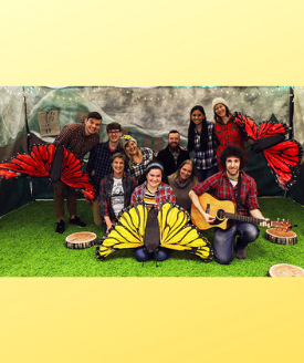 actors in plaid shirts holding giant butterfly puppets and guitar