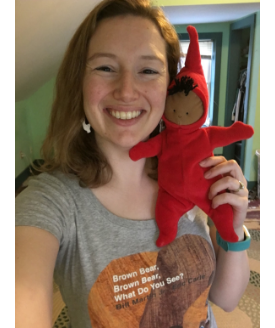 """woman wearing """"brown bear, brown bear, what do you see?"""" t-shirt holds a doll of peter from """"the snowy day"""" to her face"""