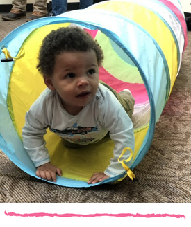 child with brown skin and curly hair crawling out of a collapsible play tunnel