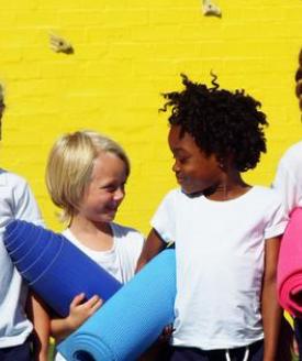 two children holding yoga mats